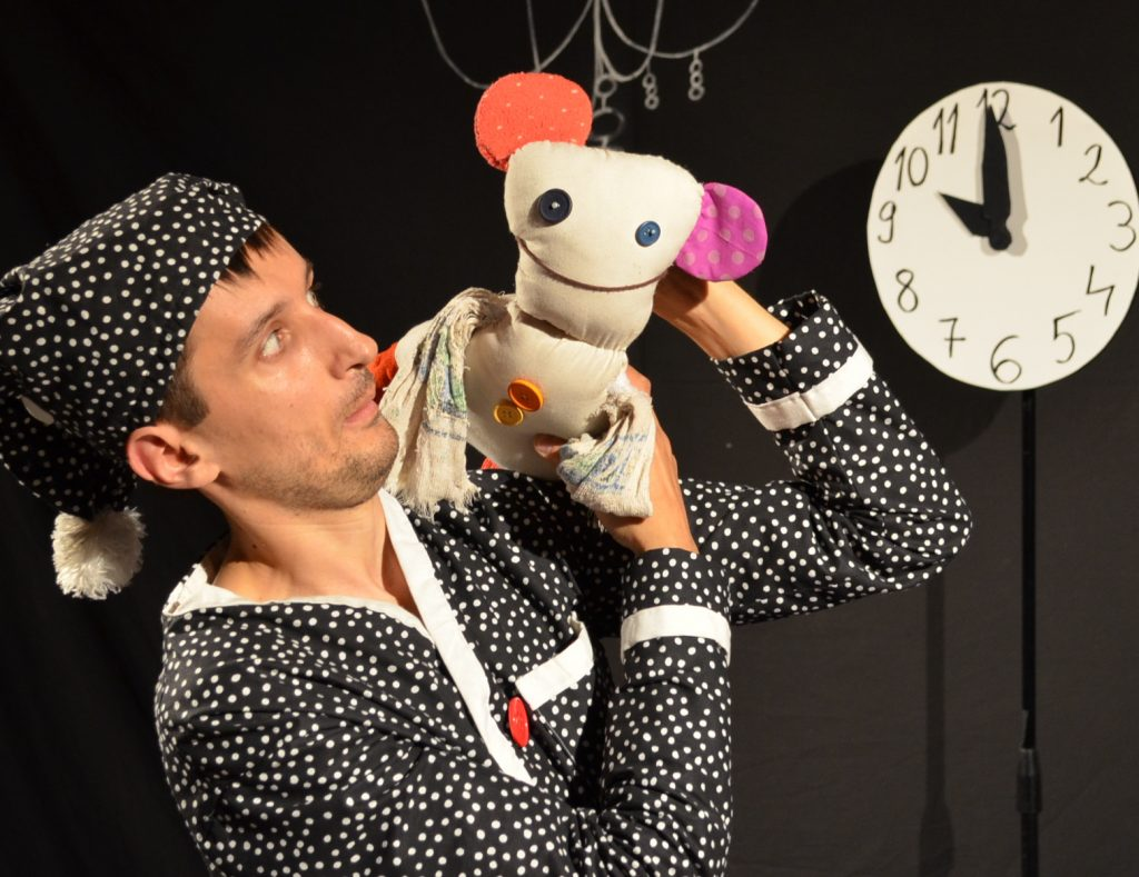 Csaba Raduly in a black and white polka dot PJ with his puppet on his shoulder as part of the show named Bed time by Puzzle Theatre.