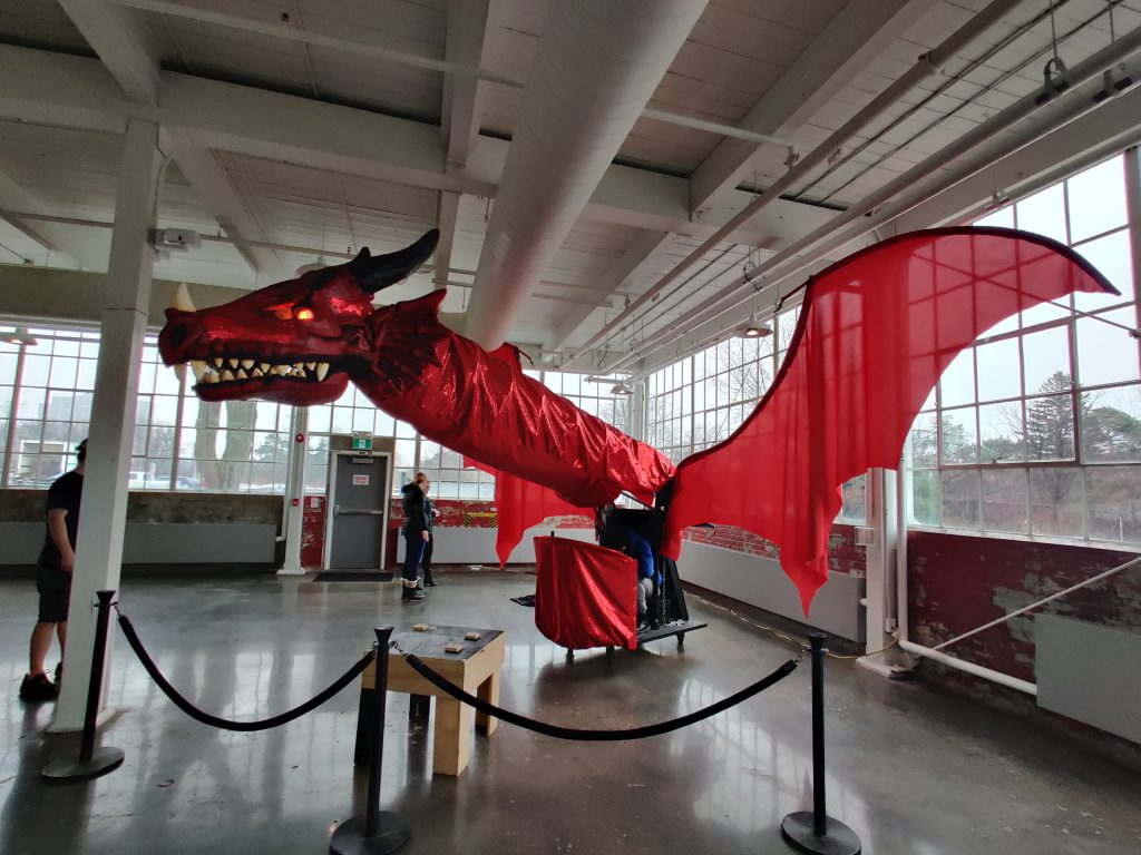 Side profile of a large red dragon puppet made by Erindale Theatre at the University of Toronto Mississauga being set up by a team of artists.