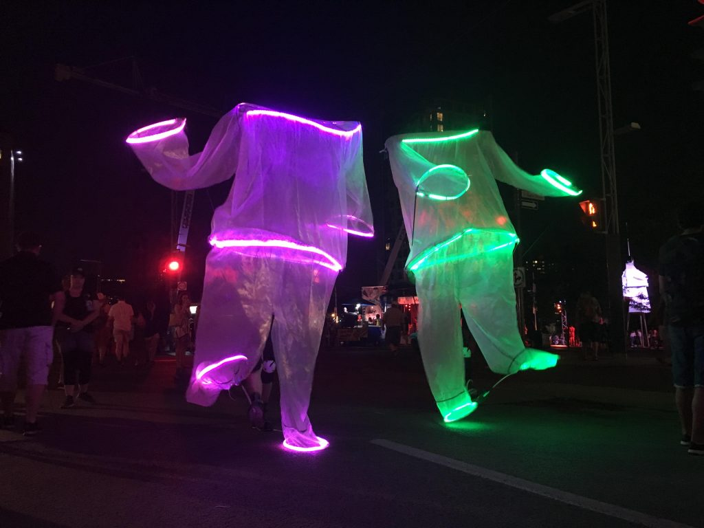 Bridges Festival present Frederic Nadeau and Mathieu Aumont controlling two large light up dancing puppets at night in a crowded outdoor gathering during march break