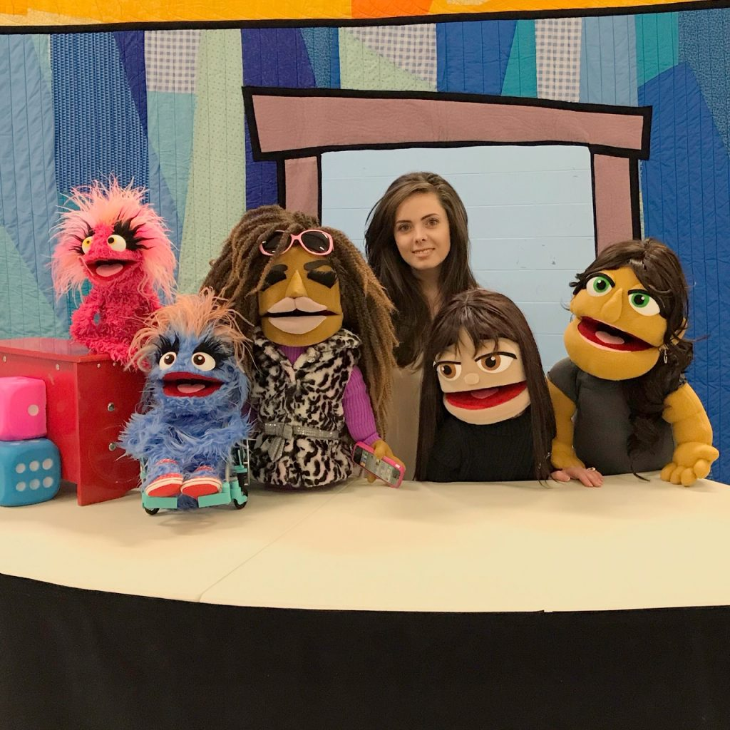 Bridges Festival presents a puppeteer from Steven Botelho's Our Space next to her five puppets during march break