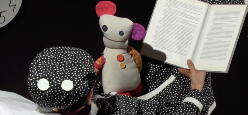 Bridges Festival performer Csaba Raduly lying down in a black and white polka dot PJs reading to his puppet as part of the show named Bed time by Puzzle Theatre during march break