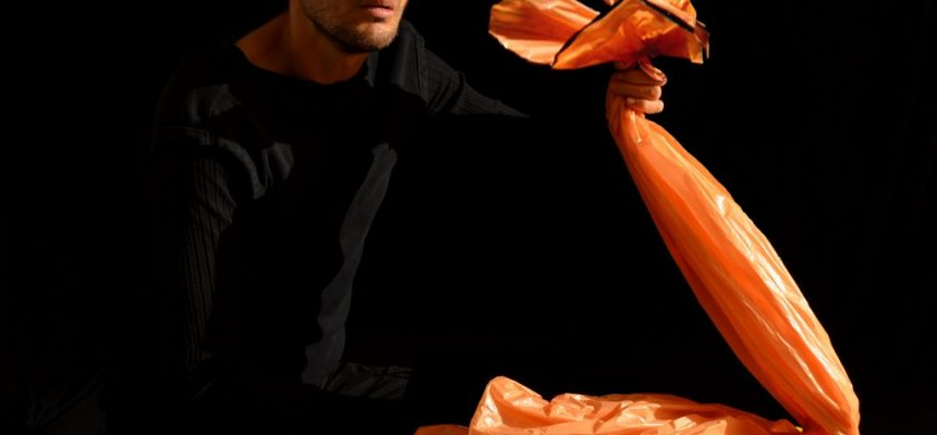 Bridges Festival artist Csaba Raduly holding an orange plastic bag puppet during the show Plastique presented during march break