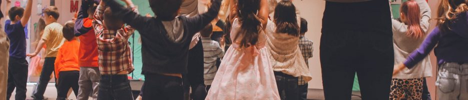 Children and parents jumping and clapping their hands above their head during a creative dance workshop.