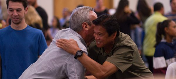An elderly man hugs another man in a community gathering with people of several walks of life socializing in the background.